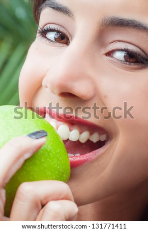 Young woman's face closeup eating a green apple