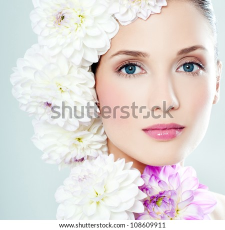 young woman's face surrounded by flowers - stock photo