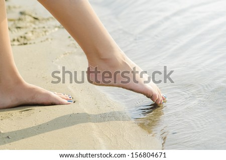 Young woman's feet dipping slowly in the water.
