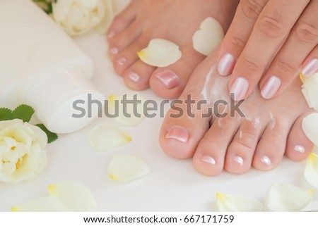 Young woman's feet with moisturizing cream. Smooth skin. Spring and summer atmosphere with fresh and fragrant white roses.