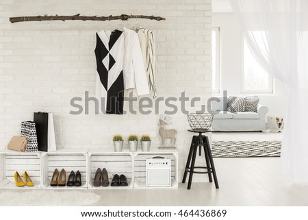 Young Womanu0027s Hallway Arranged In Black And White, With Recyclable Furniture  And Clothing Items,