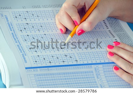 Young woman's hands filling in standardized test form - stock photo