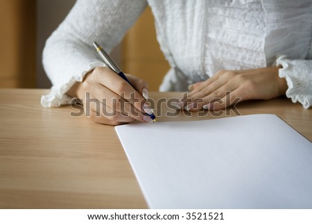 Young woman's hands holding a pen signing a blank page. - stock photo
