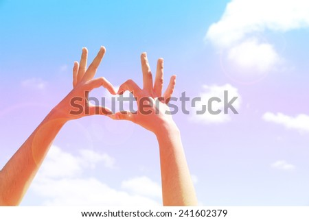 Young woman's hands making heart shape frame on blue sky background - stock photo