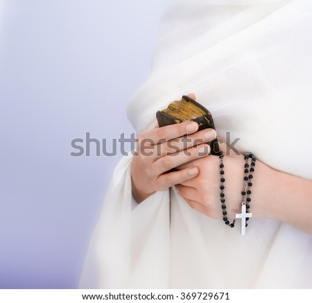 Young woman's hands with a rosary, bible and a white clothing in a background - stock photo