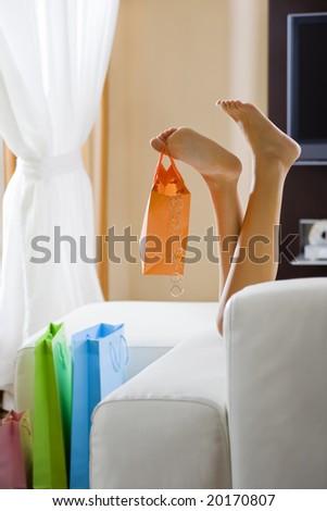 Young woman's legs dangling shopping bag - stock photo