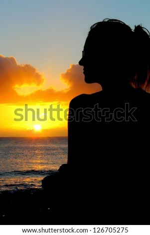 Young woman's silhouette in front of a wonderful sunset in Fernando Noronha Island, Brazil