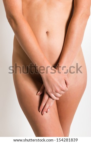 Young woman's torso with hands over her crotch