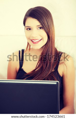 Young woman's working on laptop and smiling to camera. In home.
