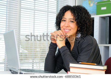 Young Woman Sat At Her Desk Using A Laptop Computer - stock photo