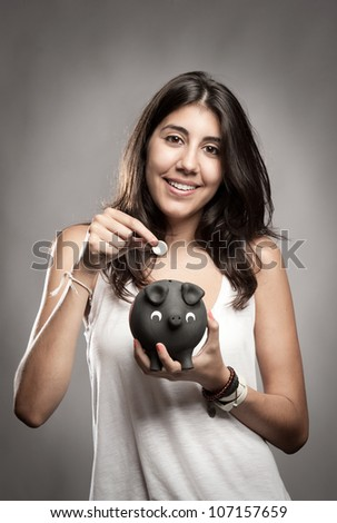 young woman saving money on a piggy bank - stock photo