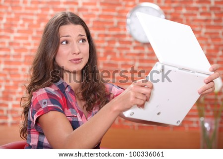 Young woman scared of her laptop - stock photo