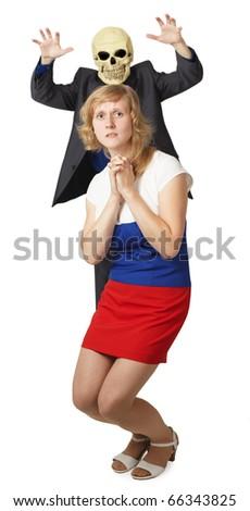 Young woman scares masked man skeleton - stock photo