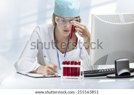 Young woman scientist examining a test tube with blood - stock photo