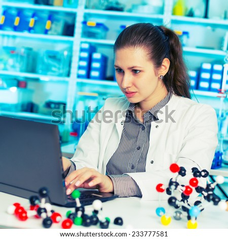 young woman scientist working at the laboratory. Model of molecule on a  table - stock photo