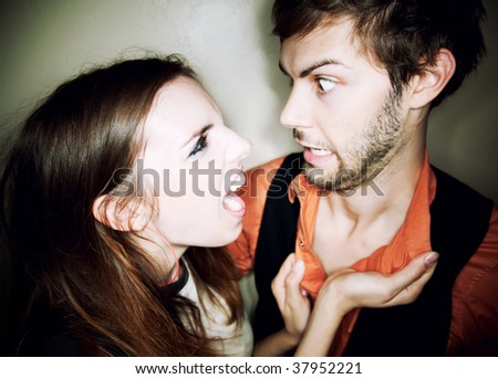 Young woman screaming at hapless bearded man - stock photo