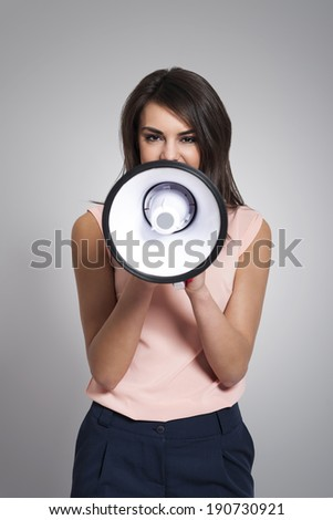 Young woman screaming by megaphone