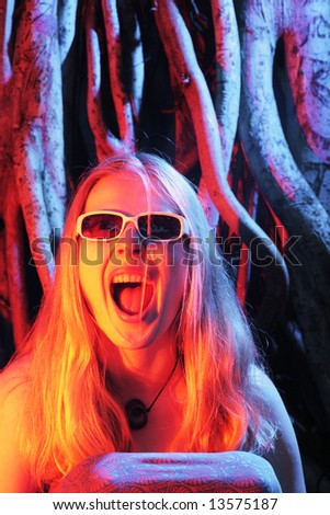 Young woman screaming in colorful dramatic light