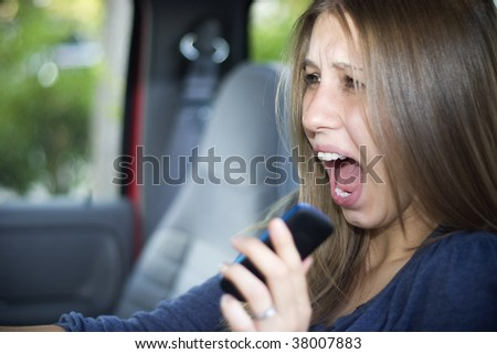 Young woman screams while driving a car. - stock photo