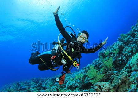 Young Woman Scuba Diver explores a Coral Reef in the Red Sea