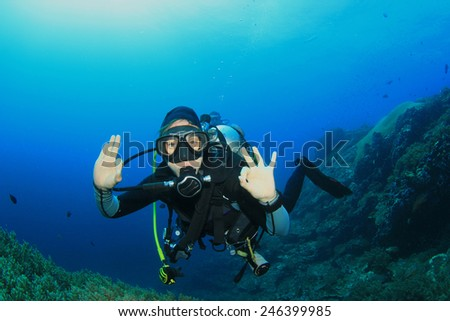 Young woman scuba diver explores coral reef - stock photo