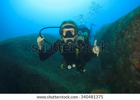 Young Woman Scuba Diver exploring underwater ocean - stock photo