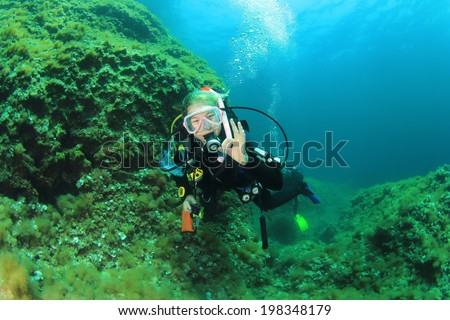 Young woman scuba diving - stock photo