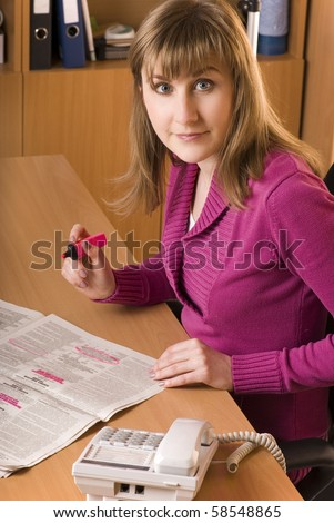 Young woman searching a job at a Newspaper Want Ad - stock photo