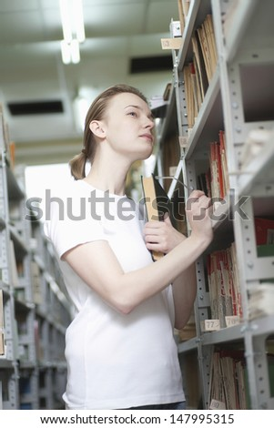 Young woman searching through the books in several bookshelves