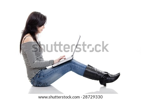 Young woman seated on the floor working with a laptop - stock photo