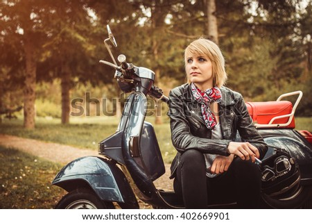 Young woman seating on a scooter motorcycle wearing casual motorcycling clothes