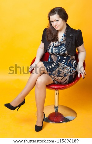 young woman seats in a red chair - stock photo