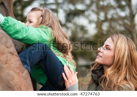 Young woman securing her little daughter while she climbs a rock - stock photo