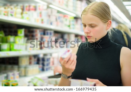 Young woman select milk products in supermarket - stock photo