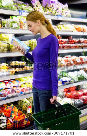 young woman selecting product from supermarket - stock photo