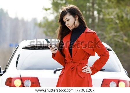 Young woman sending an sms to the car service. - stock photo