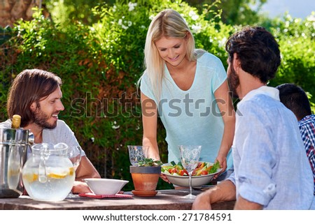 young woman serving salad to friends gathering at outdoor garden party - stock photo