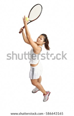 Young woman serving tennis ball