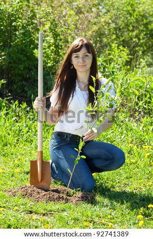 Young woman setting tree outdoor in spring - stock photo