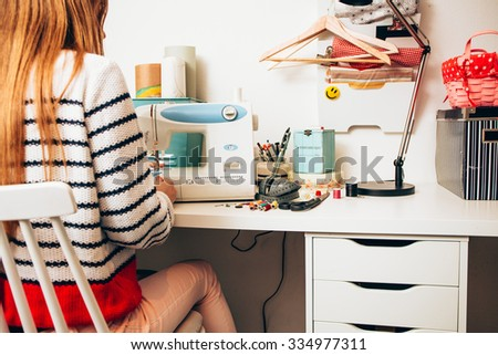 Young woman sewing on a sewing machine a garment