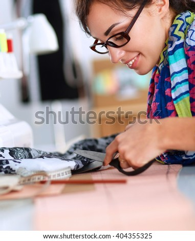 Young woman sewing while sitting at her working place - stock photo