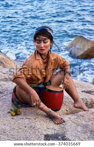 Young woman shaman in bright clothes and makeup, with drum, seating in the mountain, sea view. Ethnic fashion photo shoot. Boho style.