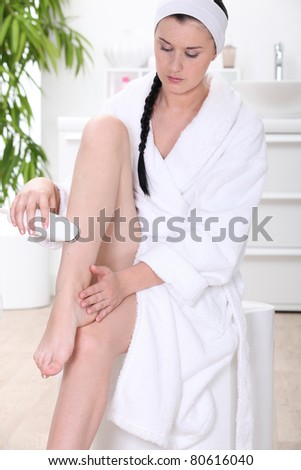 Young woman shaving legs - stock photo