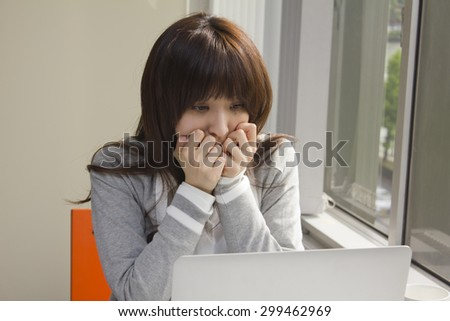 Young woman shocked in front of computer
