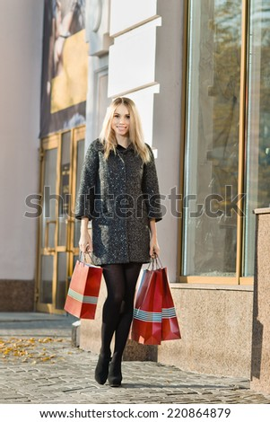 young woman shopper with red  shopping bag,  walking on street - stock photo