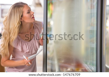 Young woman shopping at supermarket. Holding shopping list and opening fridge to pick up frozen foods