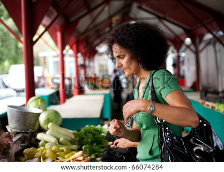Young woman shopping at the farmers market - stock photo
