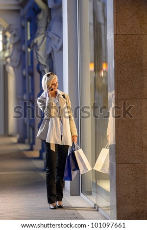 Young woman shopping evening city looking into shop windows phone - stock photo