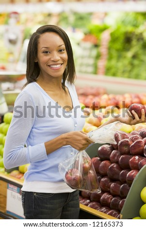Young woman shopping for fresh produce in supermarket - stock photo