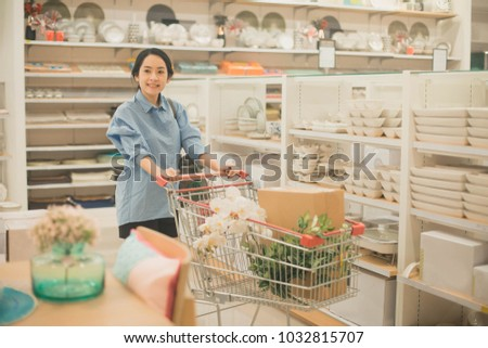 Young Woman Shopping For Furniture, Glasses, Dishes And Home Decor In Store.  Woman